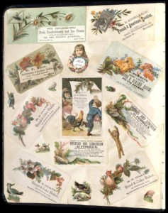 A page from a scrapbook containing several colorful cards advertising businesses and featuring flowers, animals, and children